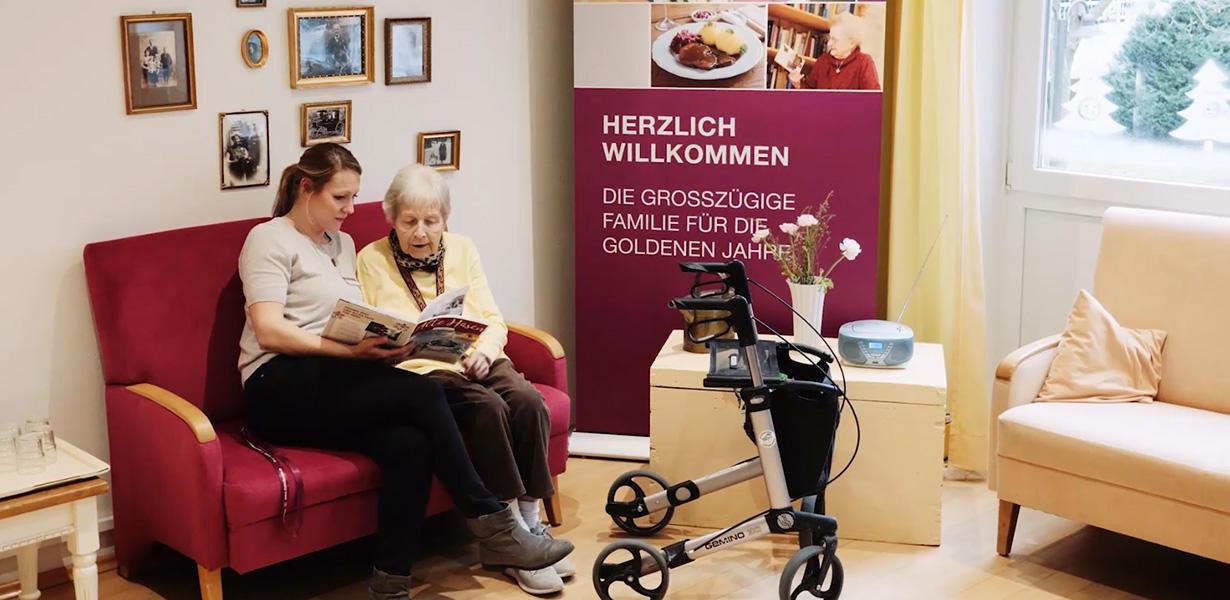 Pflegerin liest älterer Dame vor